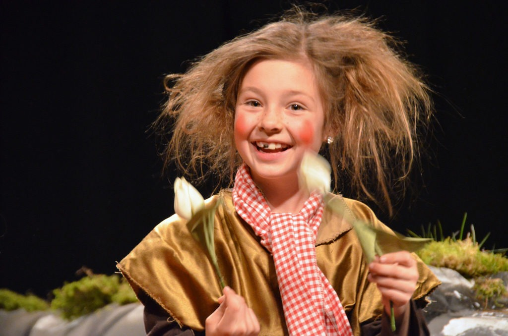 The image shows a young girl on stage. This is the kind of opportunity that is easier to find with Kids Casting.