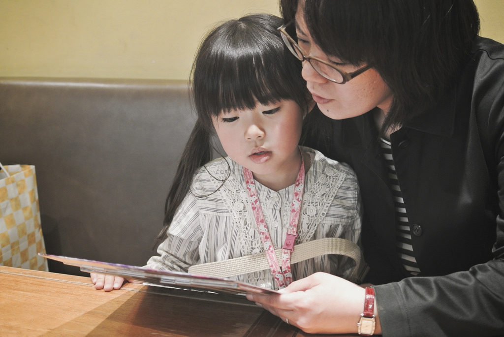 A picture of a mother reading to her daughter.